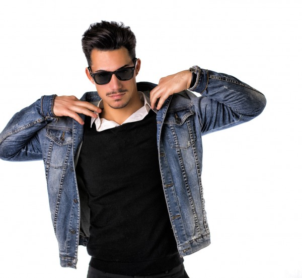 Hip, trendy young man with sunglasses and denim jacket, isolated on white